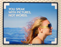 Another HP ad, showing a female in the foreground, wind blowing her hair, deep blue water behind her, and the phrase 'You speak with pictures, not words.'